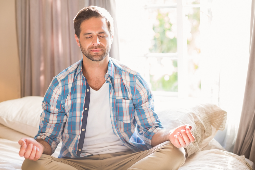 man doing yoga on his bed at home in bedroom